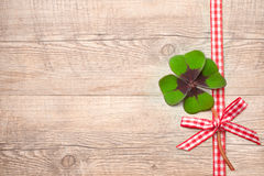 Four leaf clover over wooden background. Four leaf clover and red ribbon over wooden background stock photography