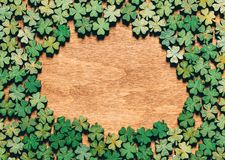 Four-leaf clovers laying on wooden floor. Creating a circle. Irish culture. St. Patrick`s Day Royalty Free Stock Image