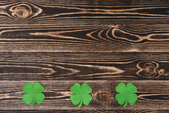 Four leaf clovers on wooden background Royalty Free Stock Photos