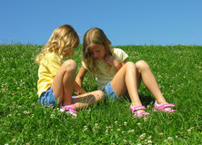 Four-leafed clover hunters. Two girls looking for a four leaf clover in the grass Royalty Free Stock Photo