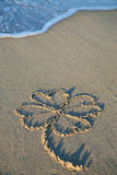 Four-leaved clover painting in the sand of a beach Royalty Free Stock Photos
