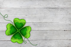Four-leaved clover on white wood. En background. Celebrating St Patricks day on March 17th. Traditional symbol of luck, happiness and wealth. Copy space Stock Image
