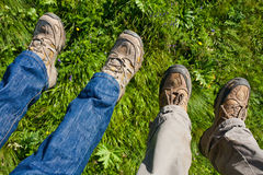 Four Legs in Hiking Boots. Legs of men and woman in hiking boots over green grass royalty free stock photography
