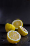 Four Lemons on Black Stone Royalty Free Stock Photography