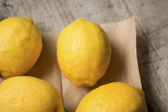 Four lemons on brown paper against a wooden background Royalty Free Stock Photography