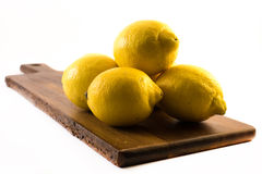 Four lemons on a wooden board on white background Stock Photo