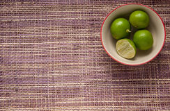 Four limes in a cup on mat background Stock Photos