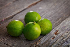 Four limes on table Stock Images