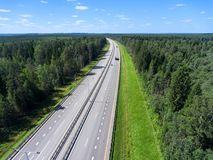 Four lines wide highway passing in green forest, vehicle drives on lane, aerial view. Four lines wide highway passing in green forest, vehicle driving on lane royalty free stock images