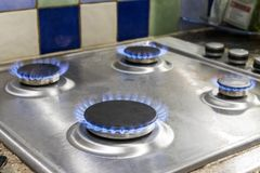 Four lit gas hobs. On a chrome stove top stock image