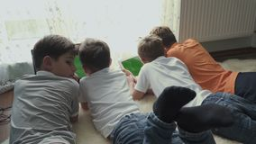 Four little brothers uses electronic gadgets at home stock video