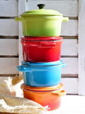 Four little colorful cooking pots, eggs and garlic Stock Images