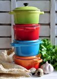 Four little colorful cooking pots, eggs and garlic Stock Photo