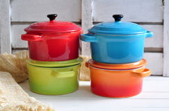 Four little colorful cooking pots and linen texture Royalty Free Stock Images