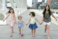 Four little girl group walking in the city Stock Photo
