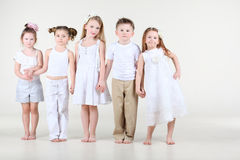 Four little girls and boy in white clothes stands. Four cute little girls and one boy in white clothes stands and hold hands Stock Photos