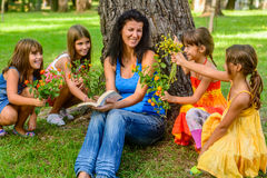 Four little girls giving mum flowers in the park. Little girls giving flowers to mother Royalty Free Stock Photo