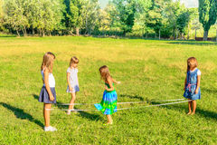 Four little girls  playing elastics in the park Royalty Free Stock Photography