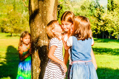Four little girls playing and whispering in the park Stock Photos