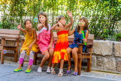 Four little girls sitting on the bench and blowing bubbles. Four little girls are sitting on the bench and blowing bubbles royalty free stock images