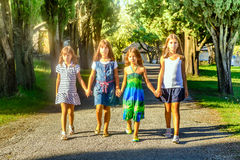 Four little girls  walking through the park Royalty Free Stock Photos
