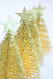 Four little gold christmas trees. In a row Stock Images