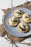 Four little homemade cupcakes pastries with lemon cream fruits almond slices icing sugar on plate Stock Images