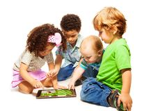 Four little kids playing tablet Stock Image