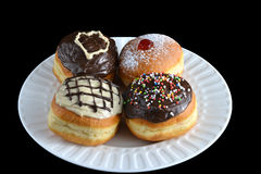 Four luxury sufganiyot with different icing on a white plate. Various sufganiyot with different icing and filling on a white plate royalty free stock photos