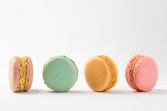 Four macaroons sweet desserts. Isolated on white background. Colorful macarons on white table Royalty Free Stock Image