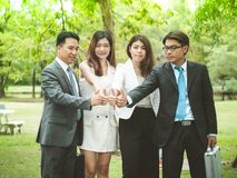 Four business people giving thumbs up. Four male and female Asian business people in park giving thumbs up signs together Royalty Free Stock Image