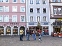 Four male street musicians play in Main Market Square in Trier, Germany royalty free stock photo