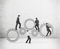 Four mans pushing gears. Four businessman pushing metal wheel and gears Stock Images