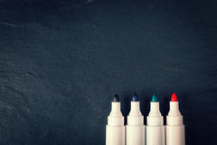 Four markers on black background Royalty Free Stock Images