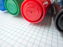 Four markers and math copybook Royalty Free Stock Photography