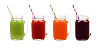 Four mason jars of vegetable juice, greens, tomato, carrot and beet, isolated Royalty Free Stock Photos