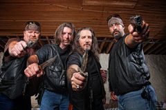 Four Mean Gang Members in Leather Jackets. Four tough middle aged white gang members with weapons Royalty Free Stock Photography