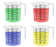 Four Measuring Jugs Full of Coloured Liquids Stock Image