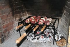 Four meat skewers being grilled on hot coals royalty free stock photography