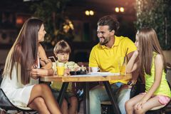 Four member family having great time in a restaurant. Four-member family having great time in a restaurant Stock Photography