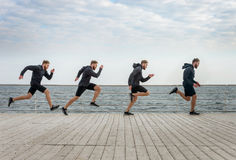 Four men clones running in sports wear along seaside Royalty Free Stock Images