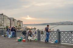 Four Men Fishing on Galata Bridge over Bosphorus Strait on Daybr. Istanbul, Turkey - Jun 28, 2015: Four men were fishing, facing Bosphorus Strait when sunlight Stock Images