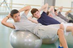 Four men leaning on aerobic balls twisting towards camera. Exercise stock photo