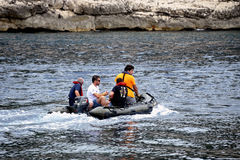 Four men at sea on a small inflatable motor boat Royalty Free Stock Photo