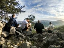 Four Men Seated on Rocks Facing Mountain Royalty Free Stock Images