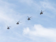 Four military helicopters Mi-35 flying diagonally Royalty Free Stock Images