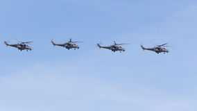 Four military helicopters Mi-35 flying formation on the blue sky Stock Photos