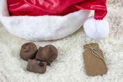 Four milk chocolate candies with christmas hat are on the white fur Stock Image