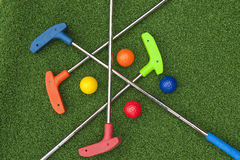 Four Mini Golf Putters and Balls. Of assorted colors laying criss crossed on artificial grass Royalty Free Stock Images