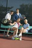 Four mixed doubles tennis players at bench at tennis court portrait Royalty Free Stock Photography